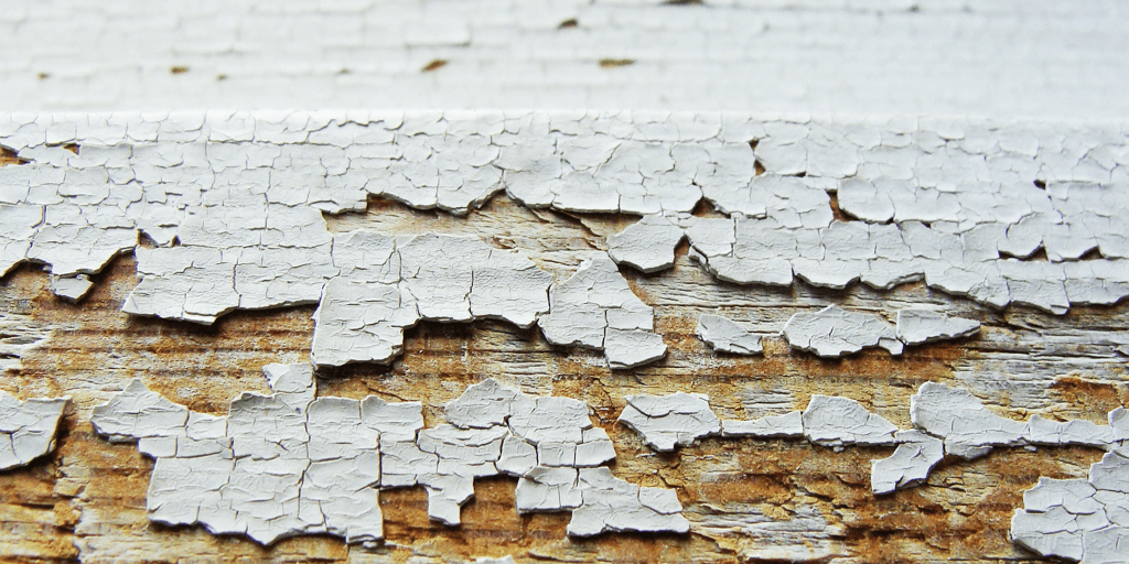 white paint chipping off wood.